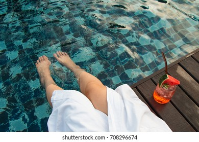a girl is sitting with watermelon drink at the swimming pool