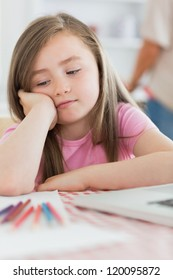 Girl sitting while looking bored with paper and colouring pencils in kitchen