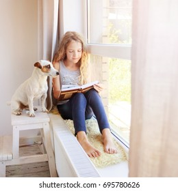 Girl sitting at window at read. Child reading book at home.