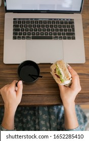 The girl sitting at a working wooden table with a laptop decided to have a snack and eat a hot tea sandwich in a black mug. Lunch break. The gadgets and technology that surround us.
