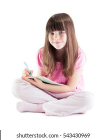 GIRL SITTING AND WRITING LOOKING AT CAMERA ISOLATED ON WHITE BACKGROUND, LITTLE STUDENT