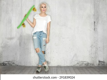 Girl with a skateboard in his hand against the background of a concrete wall