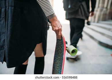 The girl with skateboard stands in the center of town