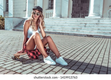 Girl skateboard, in summer city, making phone call, online application call Internet. Happy smiling, long hair longboard. Fashion lifestyle of youth. Concept ideas weekend getaway. Free space