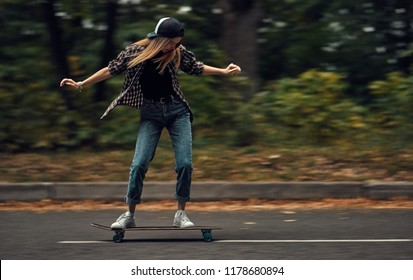 A girl skateboarder in a cap and checkered shirt rides a skateboard on the road in the forest.