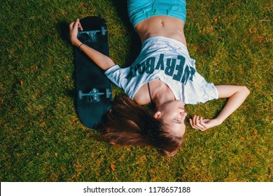 Girl skater resting on grass with her skateboard near top view