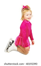 The girl skates in profile standing on knees on a white background. Very happy child in purple plum dress.