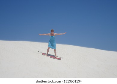 Girl skating down sand dunes on a red sandboard in Lancelin Western Australia