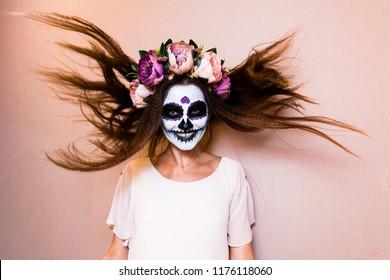 girl skeleton. Sugar skull. a dead bride. The girl in a beautiful floral wreath. Pink flowers peonies hair ornament. halloween holiday costume. happy skeleton. flying hair.