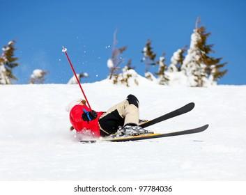 Girl skier falling down white on mountain slope