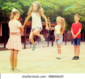 Girl skipping on chinese jumping rope and her friends standing around