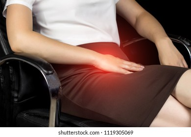 A girl in a skirt sits on a chair and holds on to the groin area, pain in the lower abdomen, sexual infection