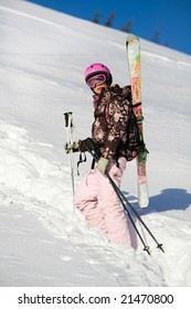 Girl with skis climbing for a freeride