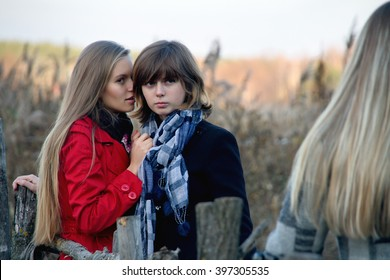 Girl slanders to his girlfriend about another girl. Three girlfriends. Girl whispers to his girlfriend about another young woman. She is gossip girl. Portrait of three young women at outdoor.