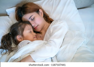 girl sleep in the bed near her mother, happy family concept