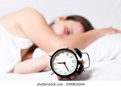 girl is sleeping in bed with alarm clock in early morning. Early to wake up the concept.