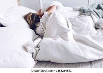 Girl sleeping in an bed with white bed sheets