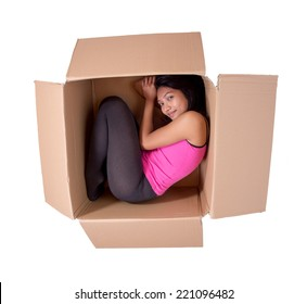 Girl sleeping in a cardboard box. Small woman lies inside a cardboard box. Woman inhabits a paper package. Woman lying in the postal package isolated on white background. Open box with a woman inside.