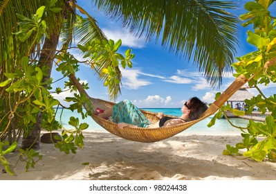 Girl is sleeping in the hammock under the palms on the tropical Maldivian beach
