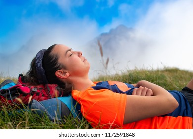 Girl sleeping with her head on the backpack in a mountain meadow during an excursion.
