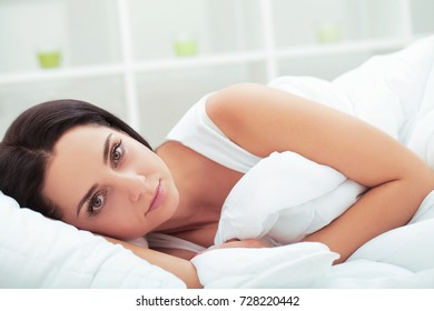 Girl sleeping in late on weekend tired from long work week resting on plush white comforter