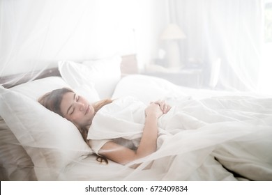The girl sleeping on comfortable white bed, happy dream in the room