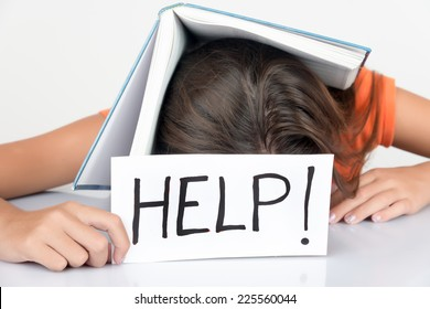 Girl sleeping with a textbook over her head and holding a sign with the word Help!
