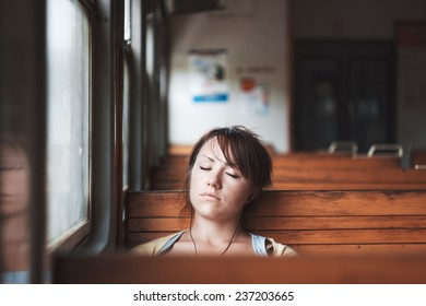 Girl sleeping in train. Portrait of beautiful brunette. Listen to music on trip. Journey by rail