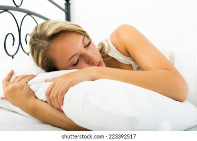 girl sleeping with white pillow in bed