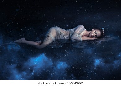 Girl sleeps in the arms of space among the stars , fantastic fotoshoot, creative color. Cold, dark, blue space, with northern lights. Sleeping Beauty. Zodiac sign. Galaxy Shining lights, sparkles.