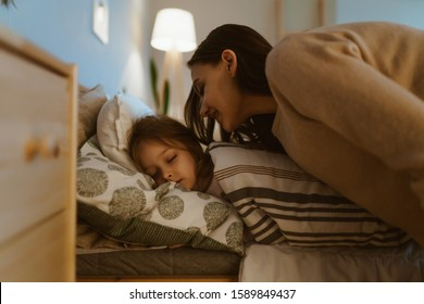 the girl sleeps in bed, mom came to wake her up and gently leaned over her