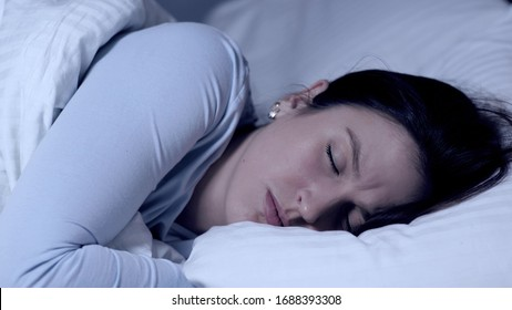 Girl sleeps and frowns. Nightmares and bad dreams concept. Young attractive caucasian girl sleeps alone in bed and experiences negative emotions from dreams. Close-up