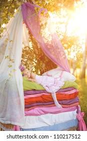 "the girl sleeps on a bed. the fairy tale ""the princess on a pea"""