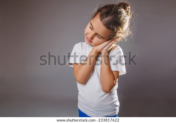girl sleepwalking smiling in his sleep on a gray background put her hands on face