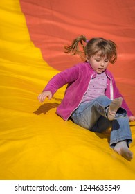 Girl sliding down on a big inflatable slide in an outdoor funfair playground