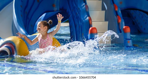 Girl Sliding in pool during vacations summer holiday