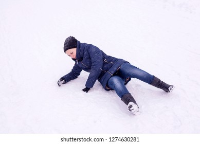 The girl slipped on ice covered with snow in the street, falling and injury in the winter