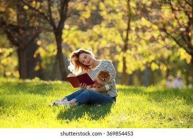 Girl with a small dog in the park Spitz