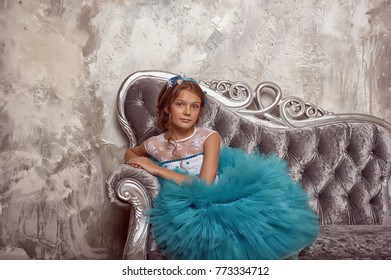 Girl in a smart blue dress with white sitting on a silver couch.