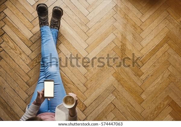 Mädchen mit Smartphone mit Kaffee auf Holzboden