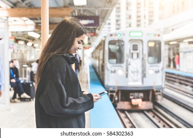 Girl with smart phone at train station in Chicago. Portrait of a young woman, mixed race, looking at the phone while waiting for the train on the platform