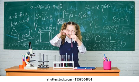 Girl smart student conduct school experiment. School pupil study chemical liquids. School chemistry lesson. Test tubes with substances. Formal education. Future microbiologist. School laboratory.