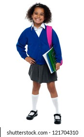 Girl in smart uniform holding notebook and calculator in hand and carrying pink backpack over shoulders.