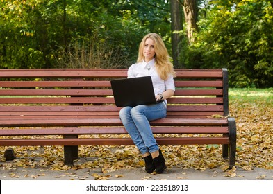 Girl with a smart-phone in an autumn park