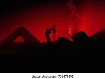Girl with smartphone and cigarette in the bed