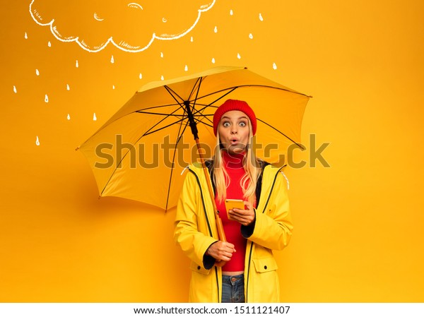 Girl with smartphone and umbrella on yellow background surprised for the weather