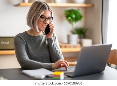 A girl smartworking from her home. The secretary working in her office. Beautiful women drink a coffee and works at the computer or laptop.
