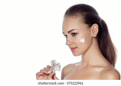 Girl smeared face cream. She is standing in profile and holding a lily flower. Beauty concept - girl with well-groomed skin.
