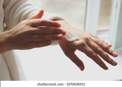 The girl smears hands with a leaving cosmetic cream for a youth and elasticity of a skin. personal care. minimalism, the top