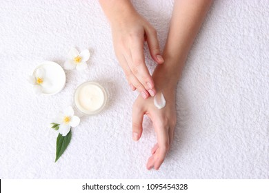 girl smears her hands cosmetic cream on the background of a towel. skin care, elastic and young skin of the hands. top view.